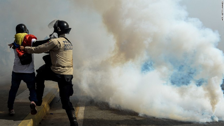 A police officer struggles with a demonstrator May 20 during an anti-government protest in Caracas.