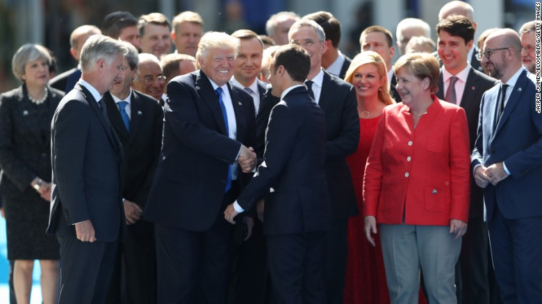 """US President Donald Trump shakes hands with Emmanuel Macron, France's new president, as other world leaders look on in Brussels, Belgium, on Thursday, May 25. They were attending <a href=""""http://www.cnn.com/2017/05/25/politics/trump-nato-financial-payments/"""" target=""""_blank"""">a NATO summit</a> as the alliance officially opened a new $1 billion headquarters."""