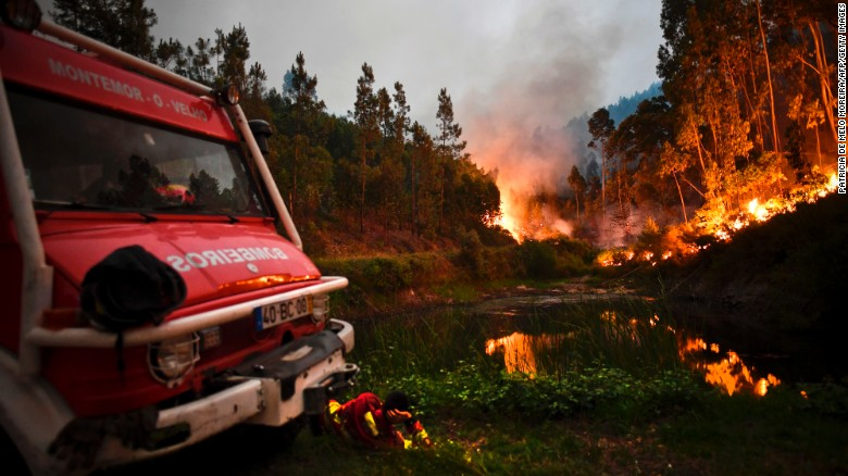 A firefighter rests next to fire combat truck during a wildfire at Penela, Coimbra, central Portugal, on June 18, 2017.