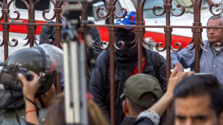 A group of hooded civilians stand outside the Parliament building in Caracas on Tuesday.