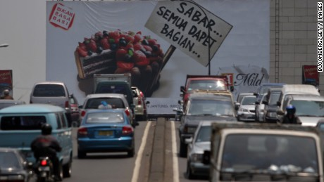 A billboard for Sampoerna cigarettes rises above traffic in downtown Jakarta, Indonesia, in 2005.