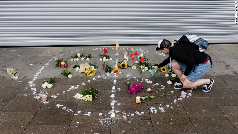 A woman places flowers  near the scene of the attack Saturday in Hamburg.