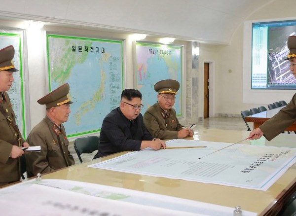 A picture from North Korea's official Korean Central News Agency (KCNA) released on August 15, 2017 shows North Korean leader Kim Jong Un (center) inspecting the Command of the Strategic Force of the Korean People's Army (KPA) at an undisclosed location. Some analysts say image on the screen appears to show runways at Guam's Andersen Air Force Base.