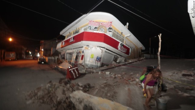A woman walks past a collapsed building in Jojutla, Morelos state, Mexico.