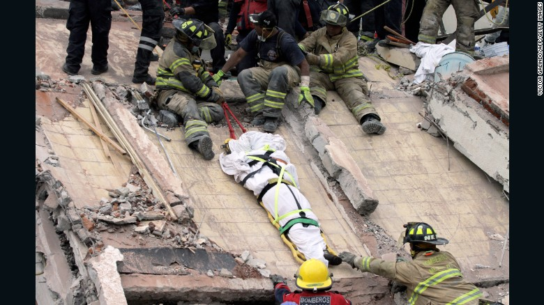 Rescuers and firefighters lower a corpse from a house in Mexico City on September 20.