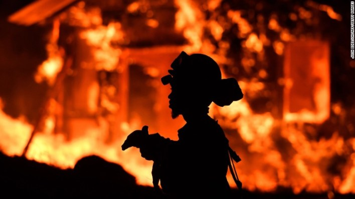An inmate firefighter monitors flames as a house burns Monday in the Napa wine region in California.