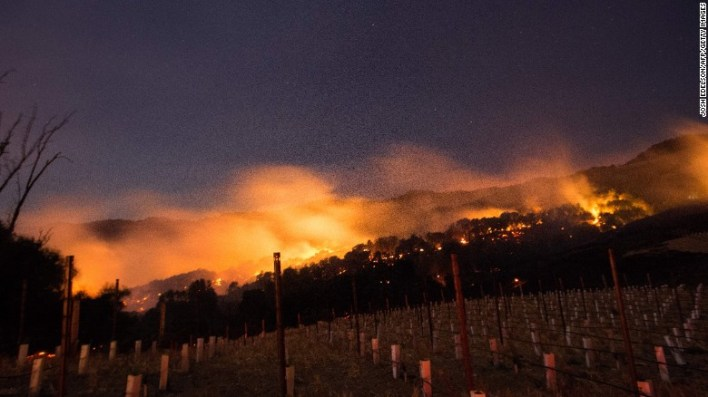 Fire glows on a hillside vineyard in Napa, California, on Monday as multiple wind-driven fires continue to whip through the region.
