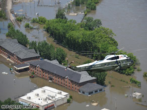 The presidential helicopter flies above flood damage on Thursday in Iowa City, Iowa.