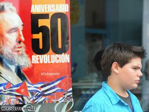 A Cuban youth passes a Havana storefront poster touting the 50th anniversary of Fidel Castro's Cuban revolution.
