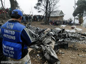 A U.N. worker at the site of the March helicopter crash that killed 10 people in Nepal.