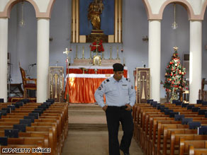 An Iraqi policeman checks security in a Baghdad church where midnight Mass will be celebrated Wednesday.
