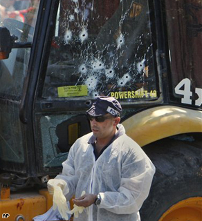 An Israeli police officer stands next to a bullet-riddled bulldozer at the scene of an attack in Jerusalem, Tuesday