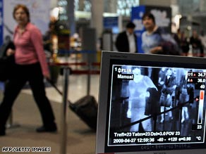 Officers check arrivals at Bangkok's main international airport as travel shares are hit by the swine flu outbreak.
