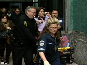Paramedics wheel Judge Cinda Fox out on a stretcher after she was attacked during court in Stockton, California.
