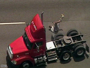 Driver Torrey Lang jumps from the vehicle as it slows to a  stop. He had been clinging to the outside of the cab.