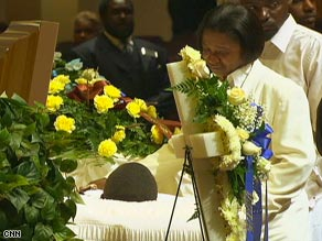 Renea Mitchell mourns over the body of her son, Robert, at his funeral.