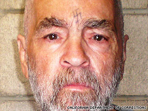 Charles Manson's mug shot shows a beard gone gray. The swastika on his forehead is still visible.