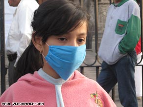 A girl in Mexico City wears a mask outside a church on Sunday.