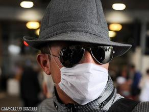 A passenger wears a face mask Thursday at Gatwick Airport in England on arrival from Mexico.