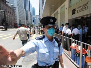 A policeman guards a Hong Kong hotel where 300 people are under quarantine.