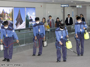 Workers in South Korea, where one case of swine flu is confirmed, disinfect a terminal Sunday at Incheon airport.