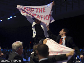 There were several protests during Shimon Peres' speech. In one of them, two people held up banners.