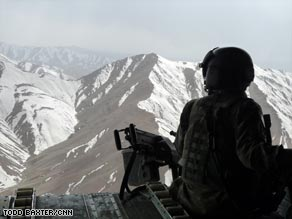 A U.S. soldier looks out of a Chinook helicopter flying over Afghanistan.