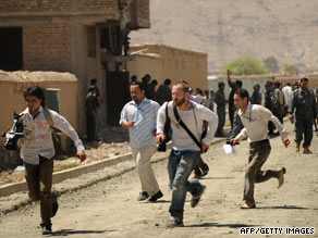 Journalists run at the site of a gunfight between gunmen and Afghan police in Kabul on August 20.