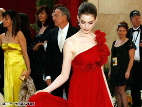 Actress Anne Hathaway adjusts her Marchesa gown as she arrives at last year's Academy Awards.