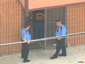 Officers stand outside the Houston, Texas, medical office of Dr. Conrad Murray.
