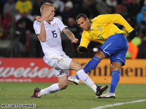 Luis Fabiano turns and shoots past U.S. defender Jay DeMerit to score his first goal of the final.