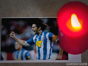 A picture of Espanyol's skipper Daniel Jarque is seen under a candle during a tribute ceremony.