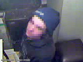 Having removed his balaclava after his efforts made him hot, the would-be burglar looks up at a security camera.