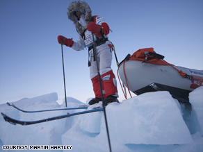 A member of the polar exploration team perches on skis inside the Arctic Circle.