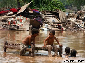 Children play in floodwater at a Pakistan refugee camp after floods displaced residents in August 2008.