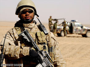 A U.S. soldier stands guard as policemen destroy poppy fields in Nadi Ali district, February 5, 2009.