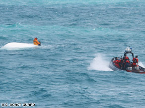 Nick Schuyler clings to an overturned boat Monday in this Coast Guard photo.