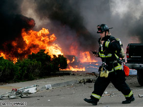 A firefighter walks past as flames rise from the wreckage of a military jet crash in California.