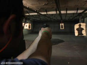 Ron Cardwell fires his 9 mm semiautomatic at a paper target at a range in Aurora, Colorado.