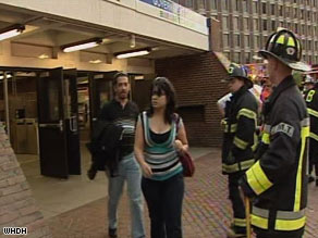 Passengers walk past firefighters at a Green Line station in Boston after the trolley collision Friday evening.