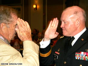 Maj. Gen. Vincent Boles salutes Berga survivor Edward Slotkin, 84, at an event in Orlando Saturday.