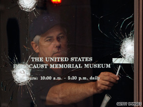 An FBI investigator looks over gunshot holes in the door of the U.S. Holocaust Museum on Thursday.