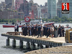 First responders gather on a pier after a plane and helicopter collided Saturday over the Hudson River.