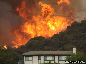 A massive wildfire burns Tuesday near a house in La Crescenta, California, near Los Angeles.