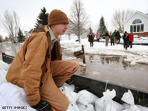 Kevin Hard rides in a trailer loaded with sandbags Wednesday in Oxbow, North Dakota.