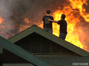 Residents stand on their roof Tuesday as a wildfire burns near their home in Glendale, California.