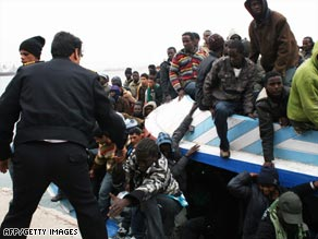 Libyan police officers help rescued migrants off an overcrowded boat that arrived this week in Tripoli.