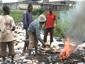 In Nigeria, men burn broken computer equipment to collect reusable metals like copper.