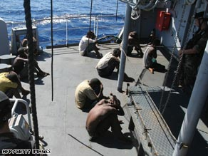 A French Navy sailor speaks to one of 11 pirates on board the French warship the Nivose after their capture.