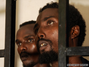Suspected Somali pirates sit behind bars during the first hearing in their trial at Aden port court on July 15.